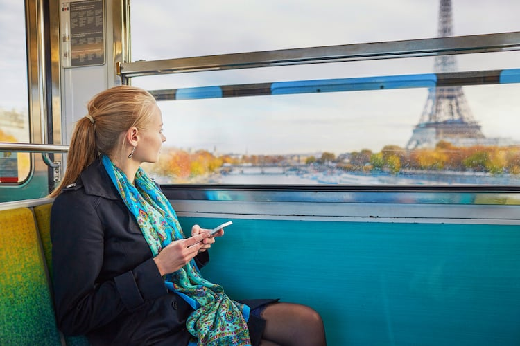 Beautiful young woman travelling in a train of Parisian underground and using her mobile phone. Eiffel tower is behind the window