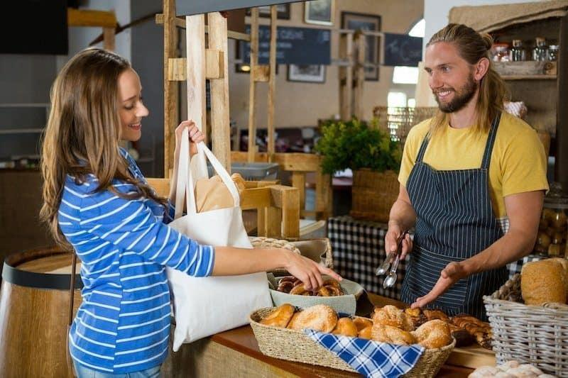Smiling female customer interacting with staff at counter