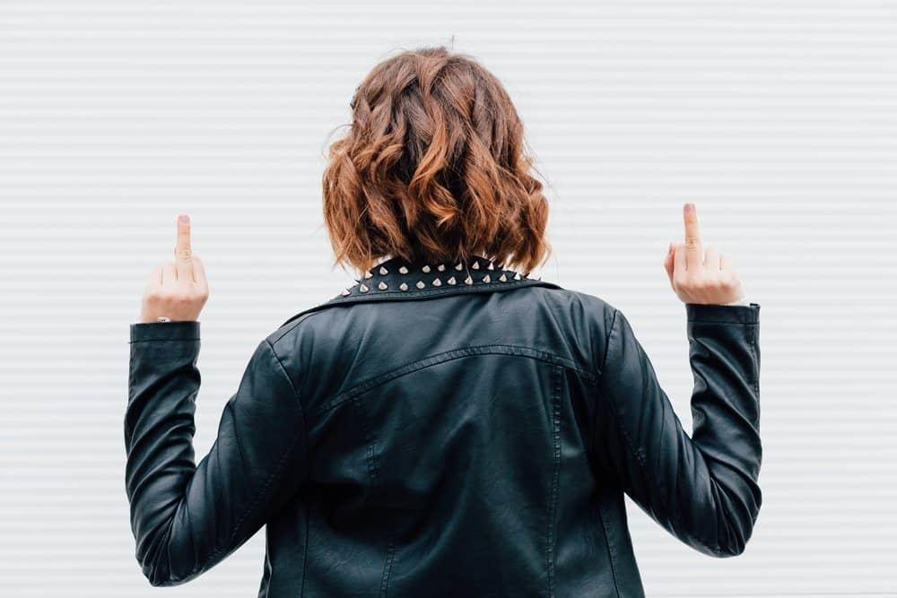 Hipster woman show middle finger, fuck you off sign in front of