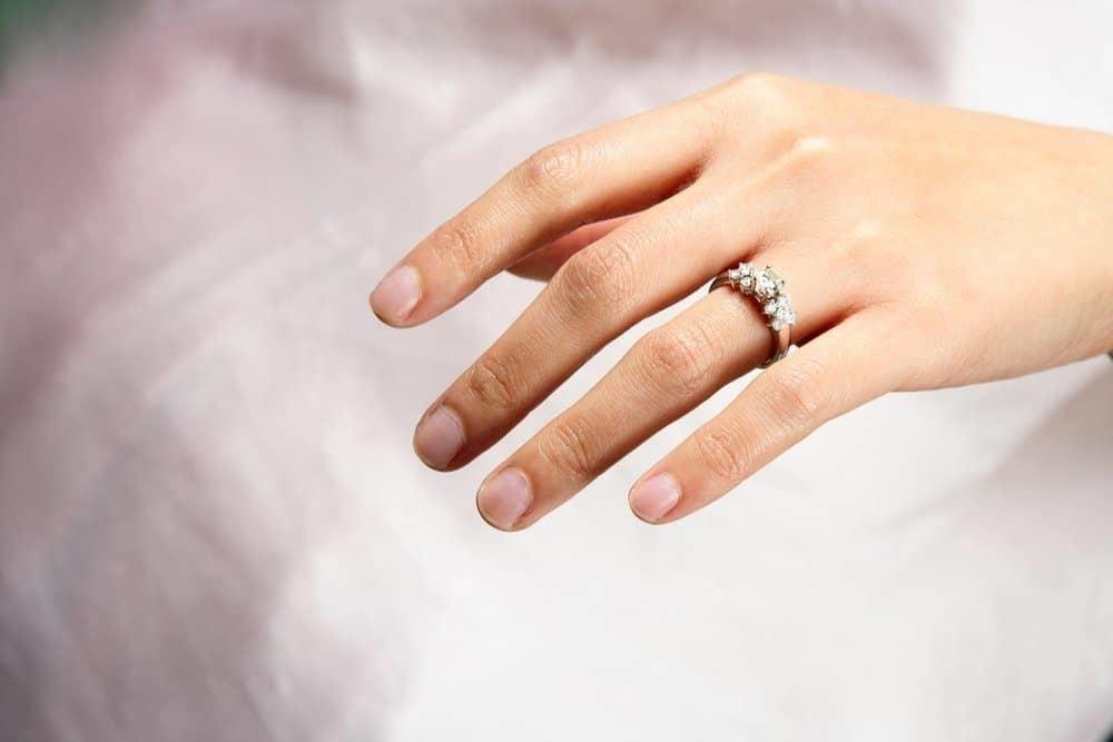 A woman hand wearing a diamond ring
