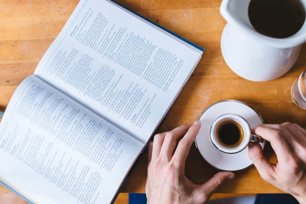 Person reading while drinking coffee