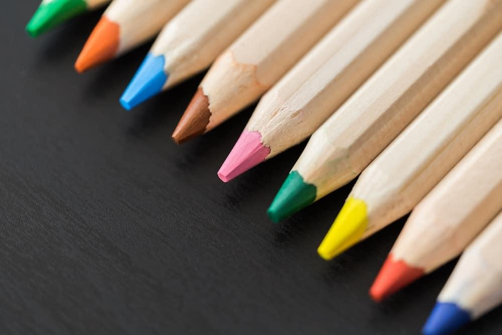 Colored-Pencils-in-a-Row-on-Black-Desk-Close-Up