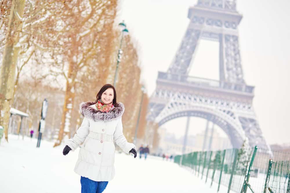 Woman enjoying snow near Eiffel Tower, Paris