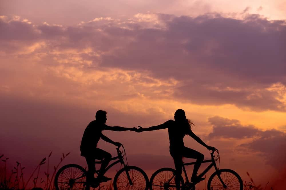 people-holding-hand-on-bike