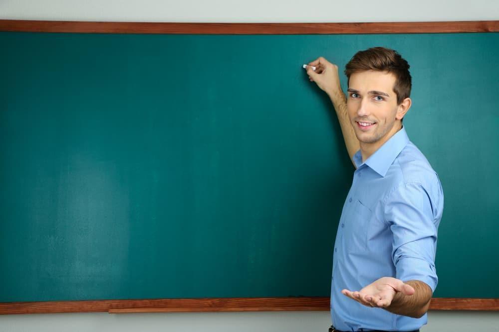young teacher near chalkboard