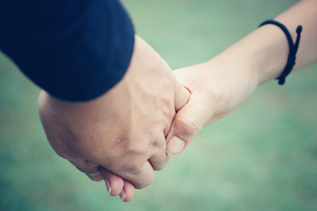 closeup of 2 people holding hand