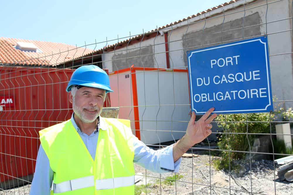 Man standing next to sign with security rules on French building site