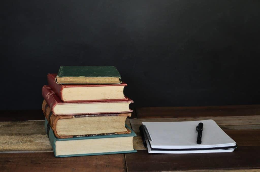 Stack of books next to notepad and pen