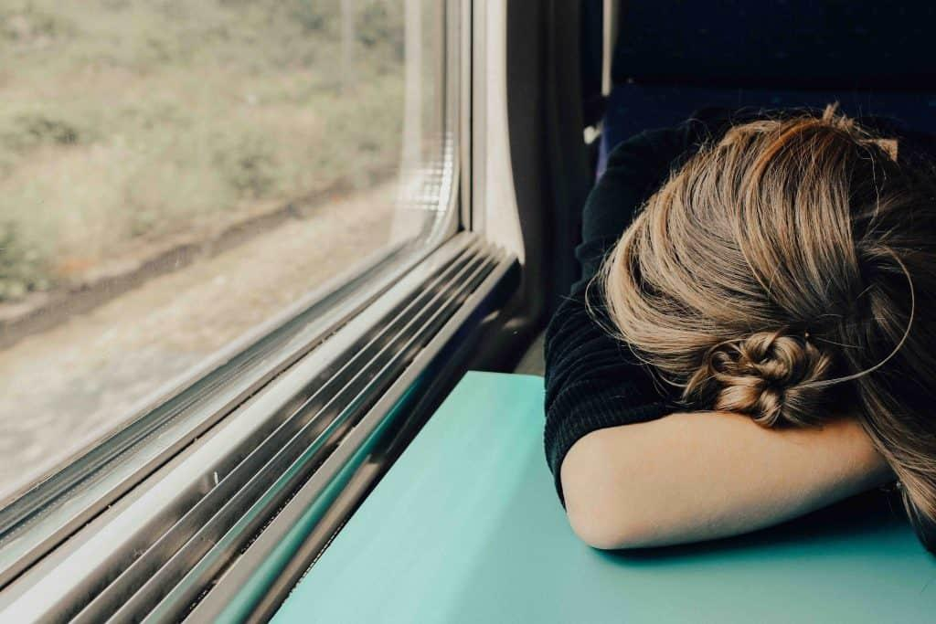 woman sleeping on table in train