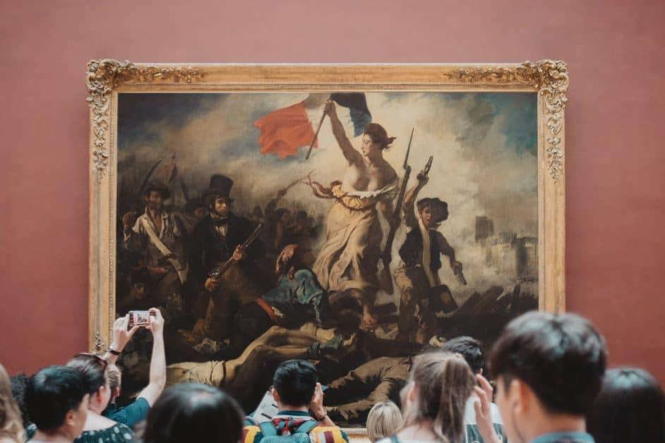 "People taking pictures of ""Liberty guiding the people"" painting in Louvre museum"