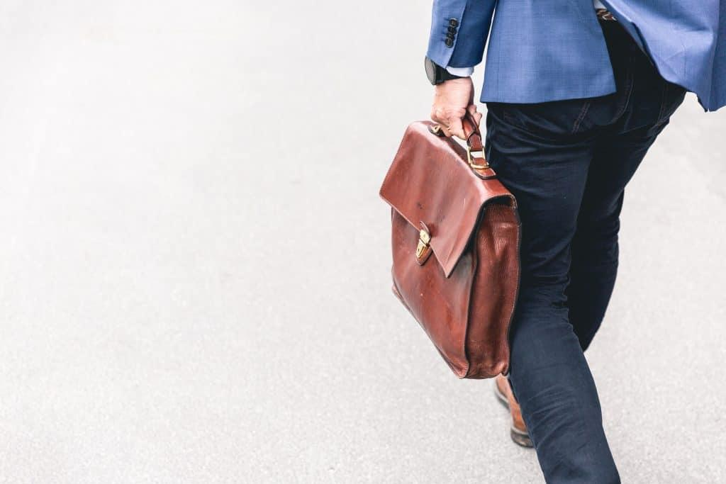 Man with suit carrying leather briefcase