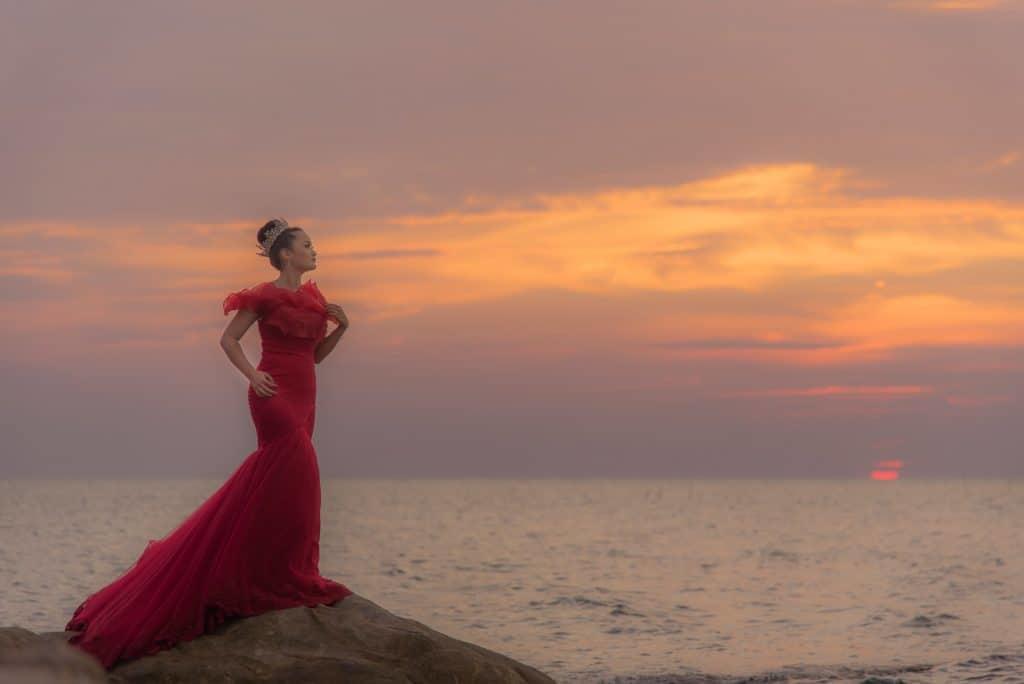 woman wearing beautiful dress on the beach at sunset