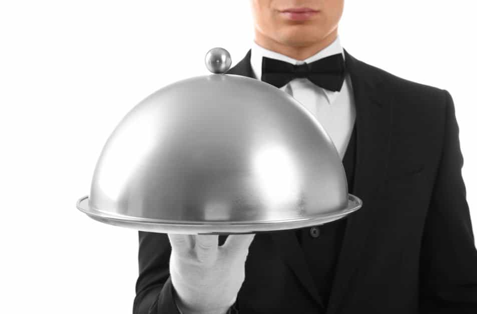 A butler holding a dish with a cloche cover