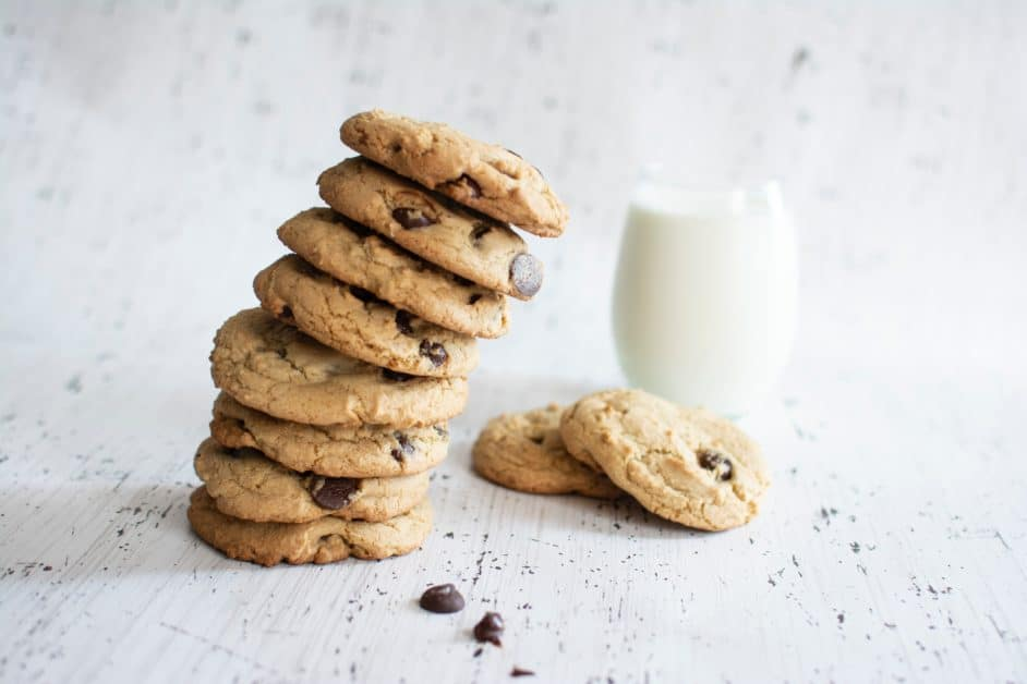A perilously leaning stack of chocolate chip cookies, with two on the table nearby with a glass of milk behind them
