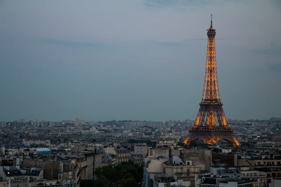 The Eiffel Tower towers over the rooftops of Paris, lit its usual orangey-yellow at twilight.
