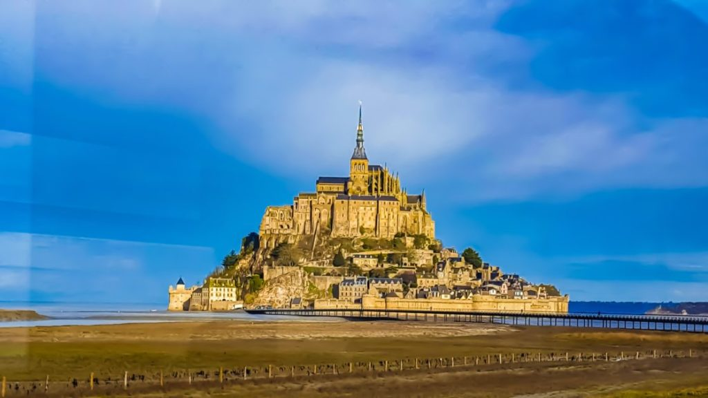 Mont Saint-Michel rises above the flat sands of the bay during low tide.
