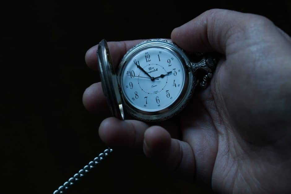 A man's hand holding an open pocket watch