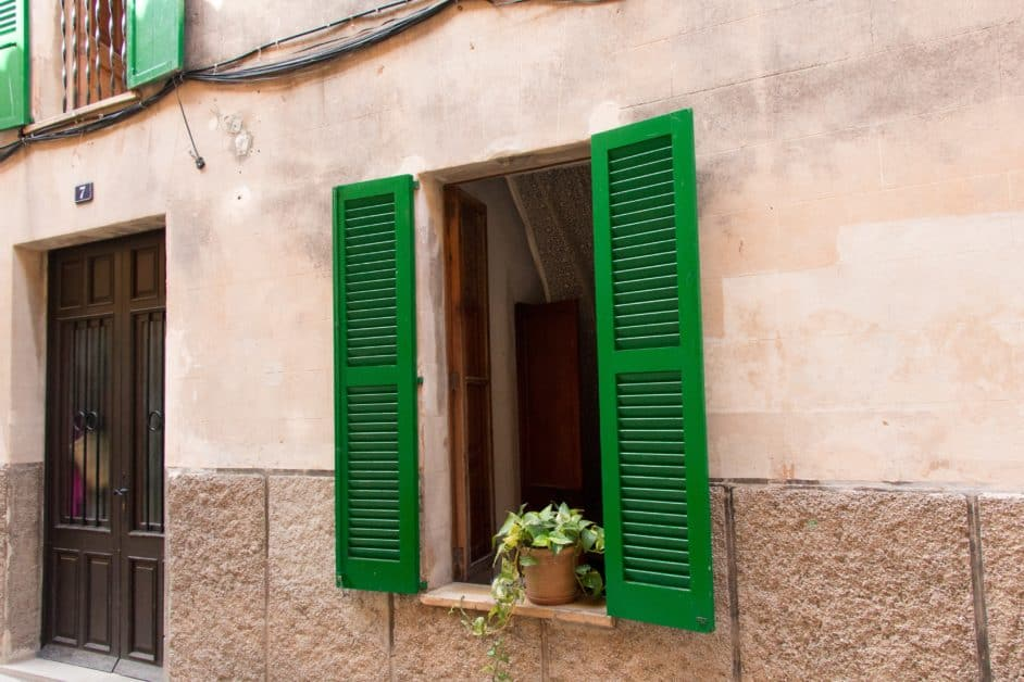 A view of a stone facade of an old-fashioned residential building, with an open window framed by green shutters.
