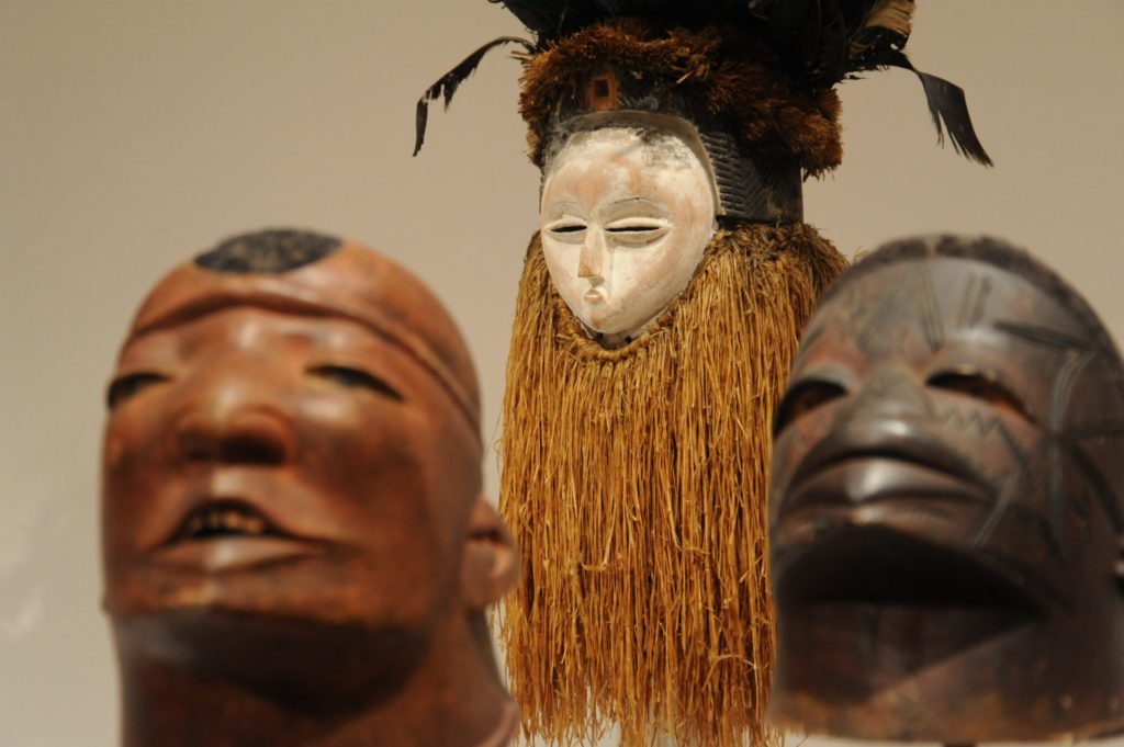 Three African masks. Two in the foreground are carved in wood. In the background, a mask has a white-painted face, dried grass haning from its chin like a beard, and an elaborate headdress made of feathers and other elements in a rich dark brown.