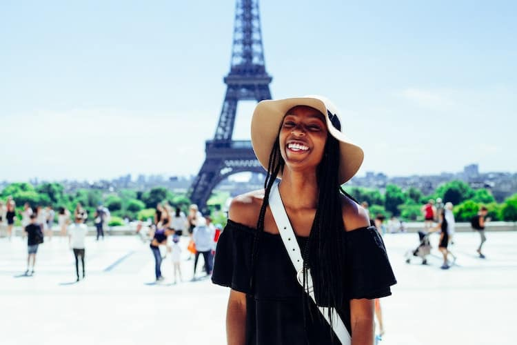 woman smiling in front of the Eiffel Tower
