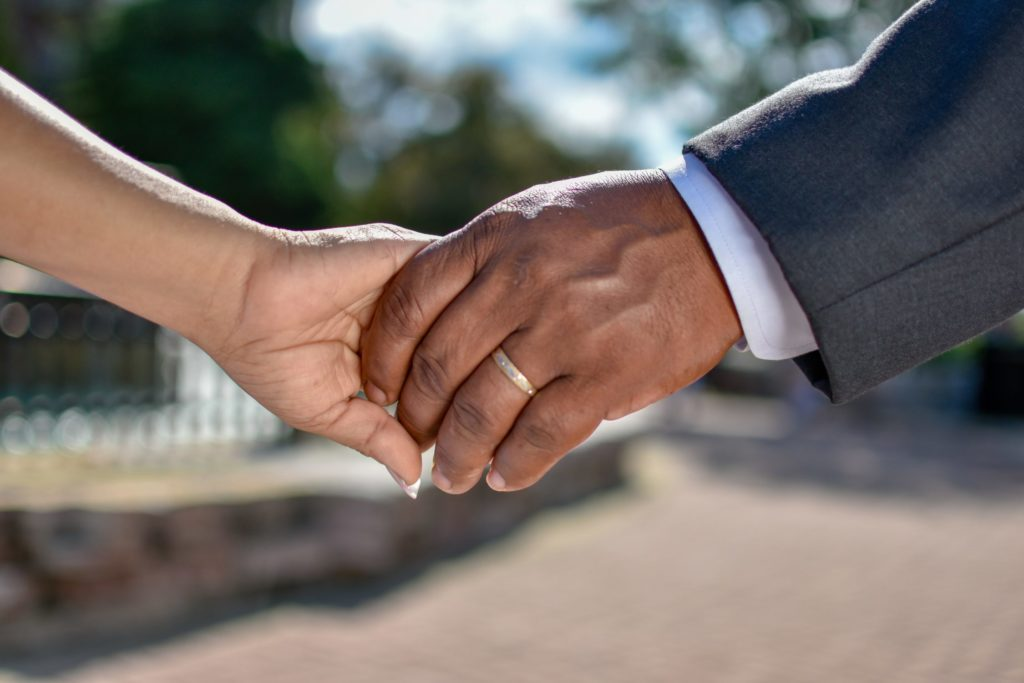 A white woman and black man holding hands. We see only their hands. The man's hand has a wedding band on it.