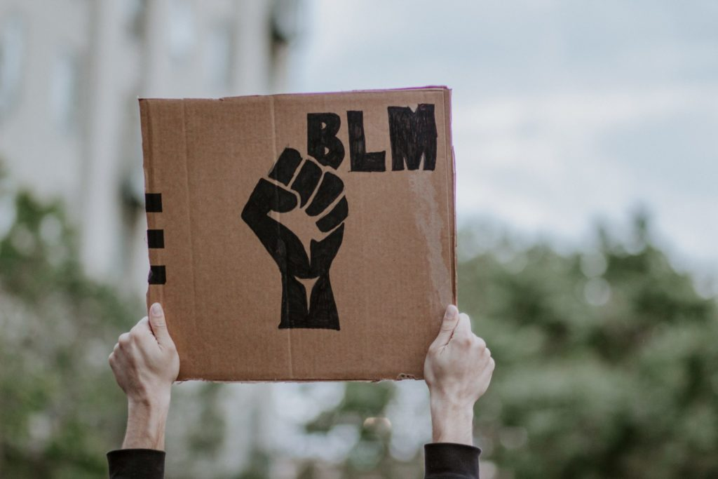 """A pair of hands holds up a cardboard sign showing a fist and the words """"BLM"""", the abbreviation of """"Black Lives Matter""""."""