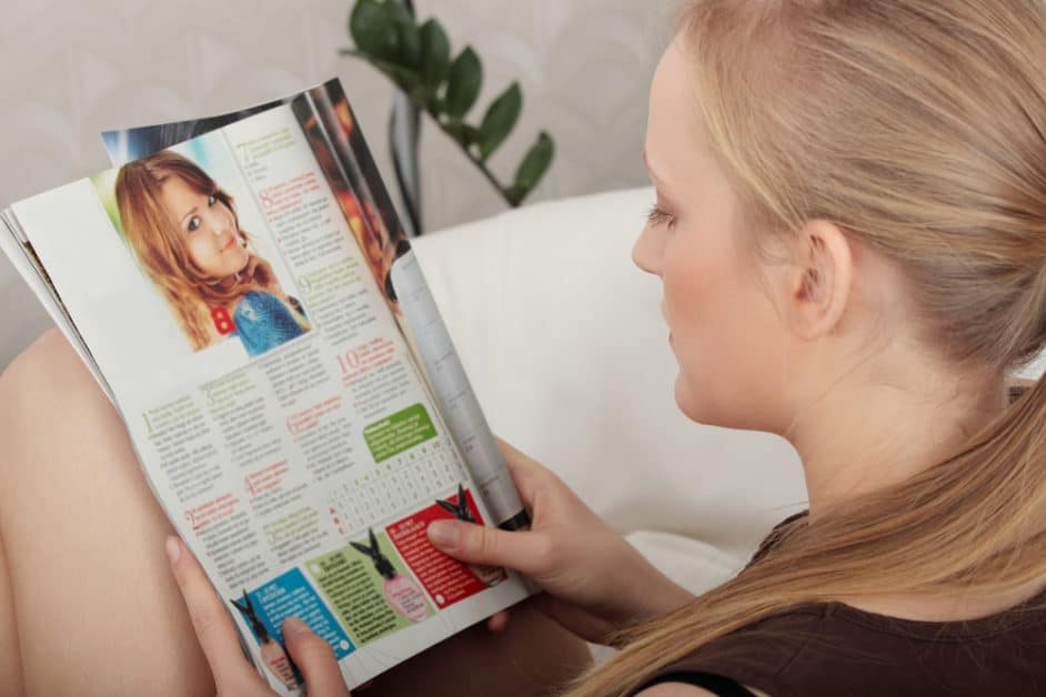 Blonde woman reading a magazine. The open page shows a 10-question quiz, with an illustration of a smiling woman. Interestingly,  each answer shows what seems to be a doney or rabbit wearing a t-shirt.