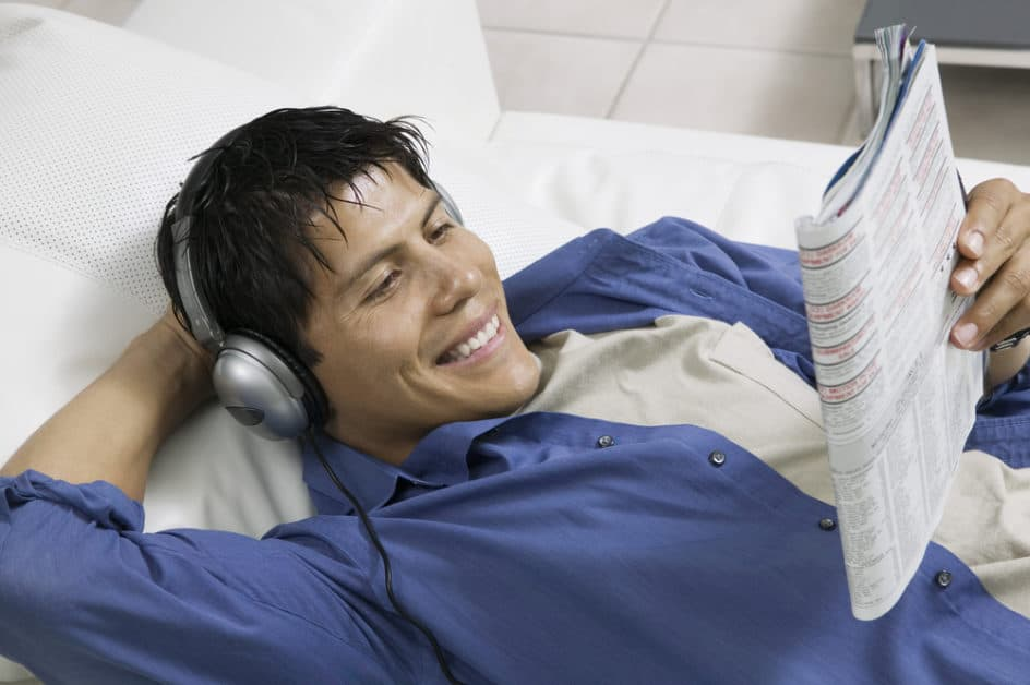 A man wearing headphones reads a magazine in bed, smiling.