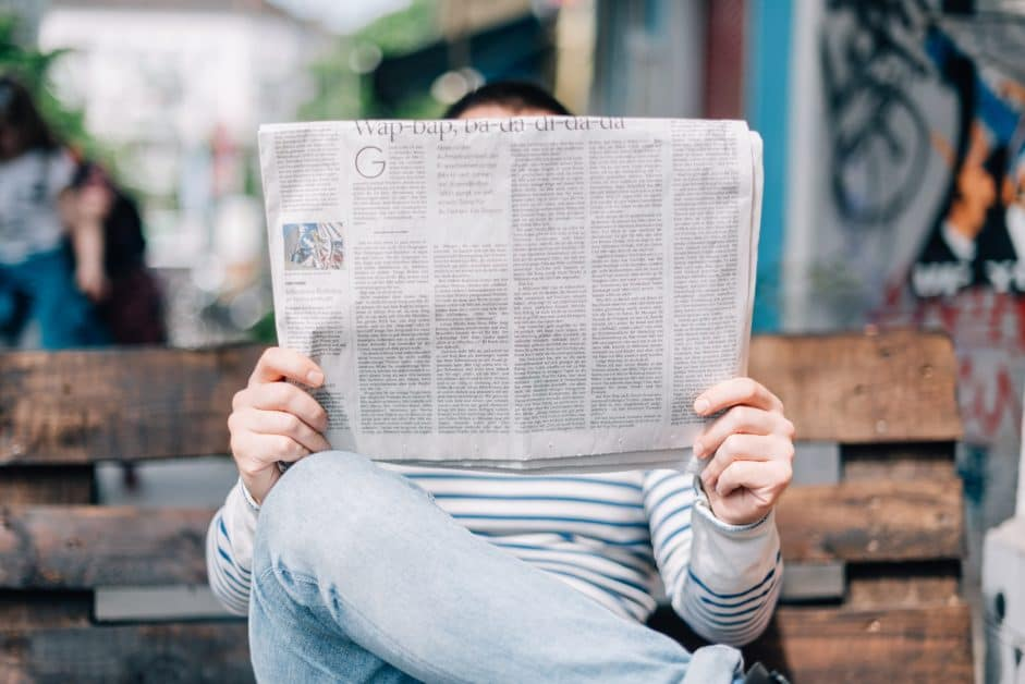 A man wearing jeans and a striped shirt sits on a bench and reads the newspaper.