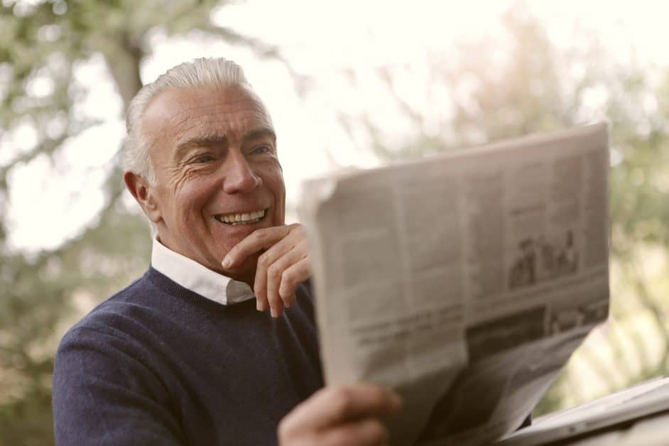 A gray-haired man reads a newspaper, smiling. I guess it's good news!