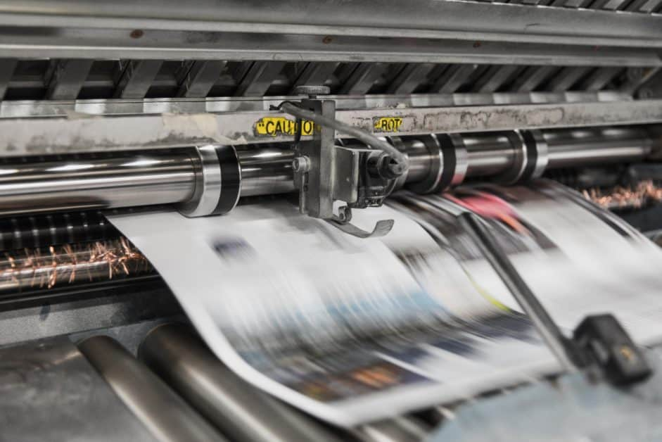 Newspapers rolling off a printing press