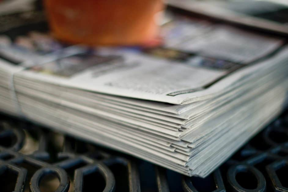 A stack of newspapers bound in string and held by someone's hand.