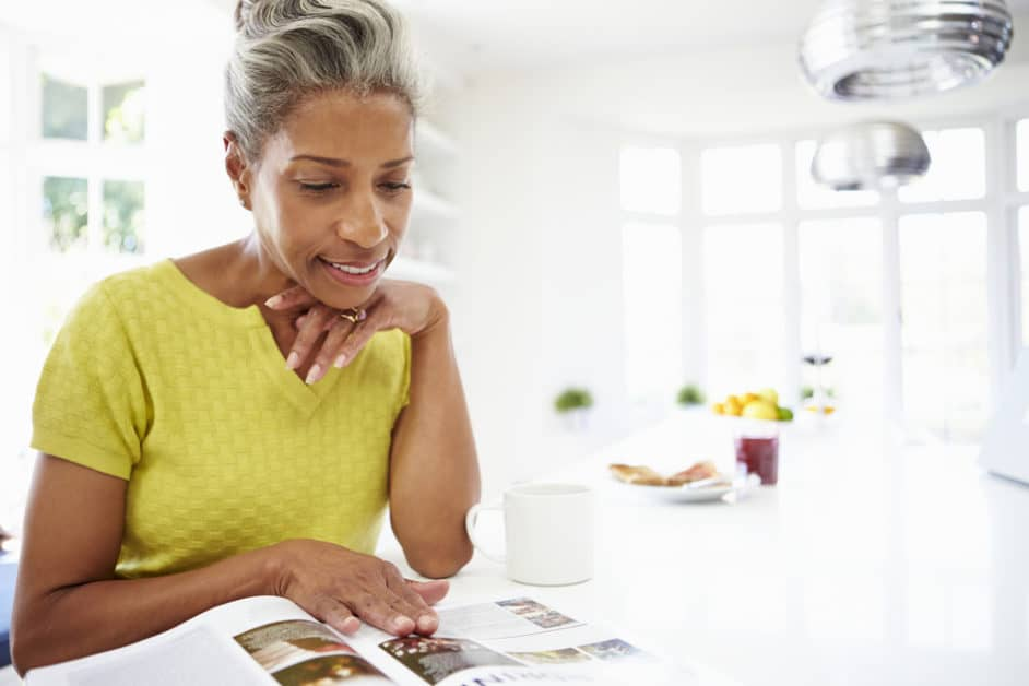 A woman reads a magazine while eating breakfast in her very bright kitchen.