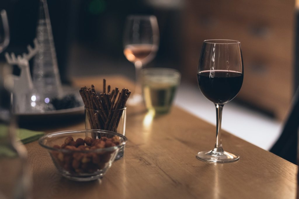On a dimly lit table, we see two wine glasses, a small bowl of nuts, and a small glass filled with pretzel sticks.