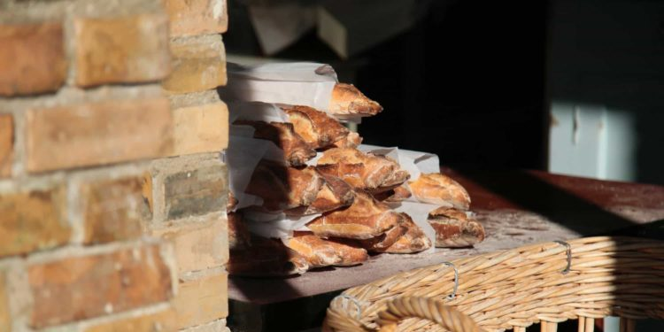 A pile of fresh-baked, crusty baguettes seem to peek out from behind a brick wall of a French restraurant.