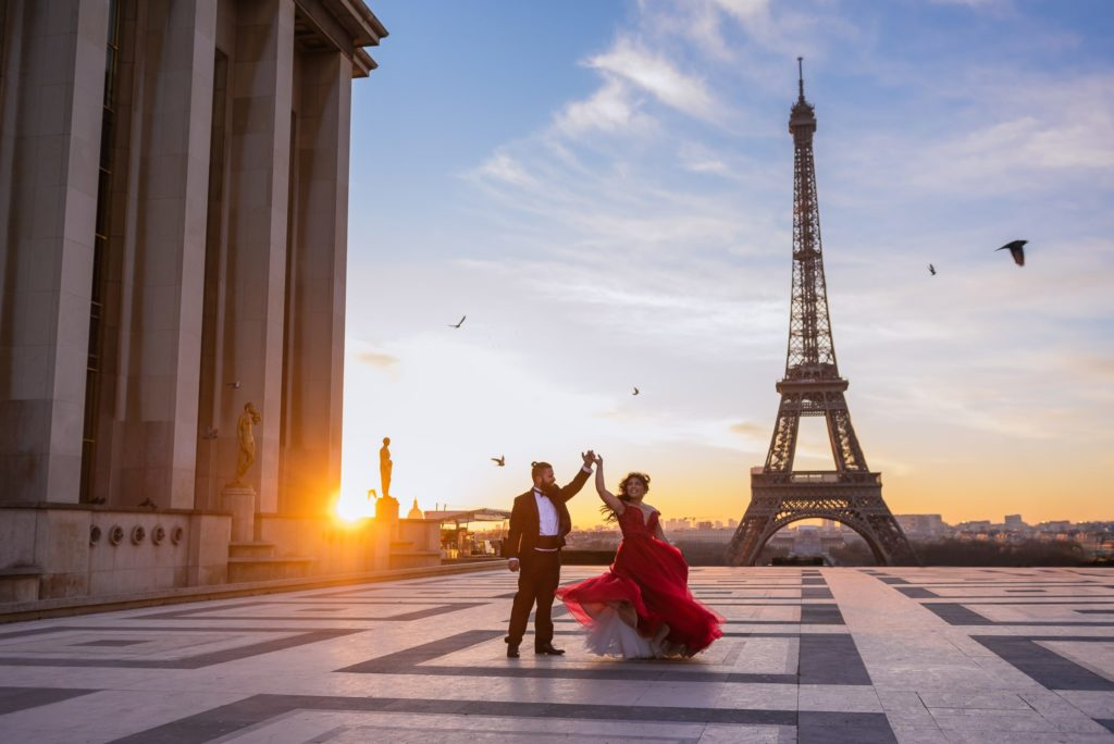 A couple in formal dress - he in a tuxedo and she in a red ballgown with a puffy white underskirt- dance on the esplanade of the Trocadero, with the Eiffel Tower in the background. The sun is setting and pigeons are flying, sihouetted against the blue sky.