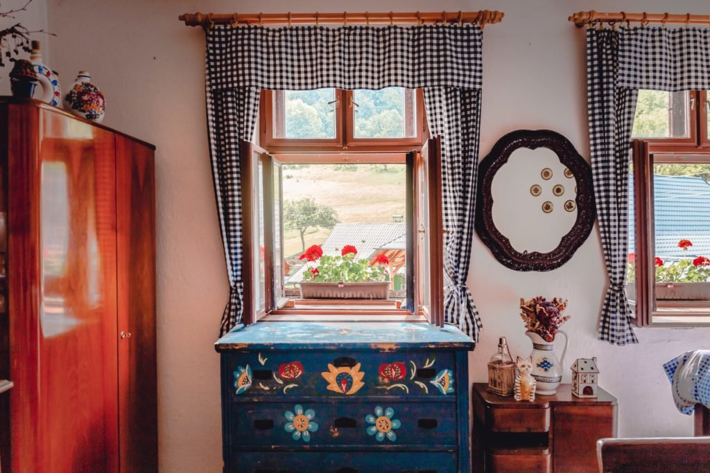 A pretty dresser painted dark blue with folk art flower designs, in a sunlit room bedroom. We see windows with black and white checkered curtains, a black picture frame, and little knick knacks everywhere.