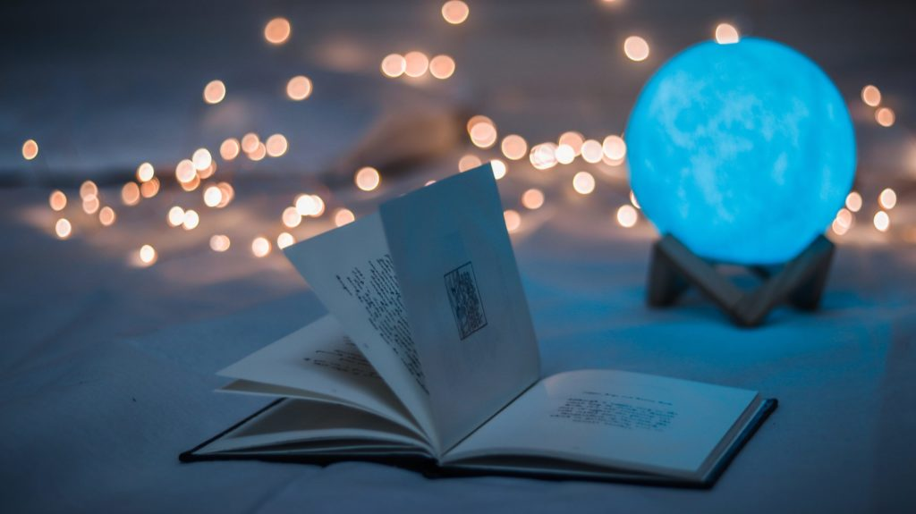 An open book, with a moon-shaped light and fairy lights in the background.