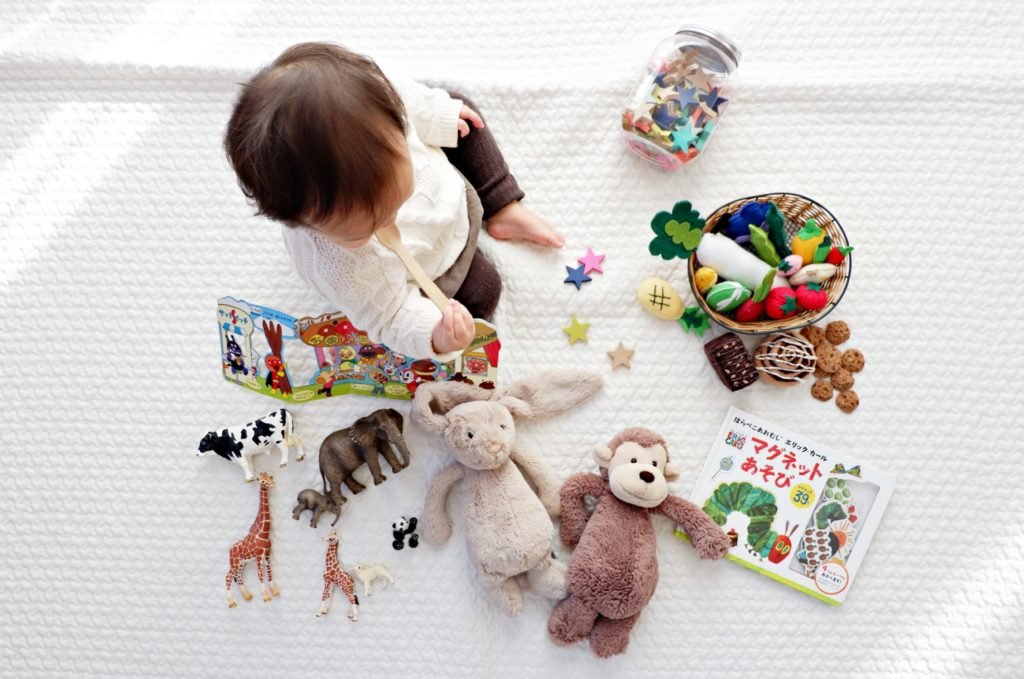 A young toddler sits by scattered toys, including stuffed animals, animal figurines, a picture book, plush veggies and dessert snacks.