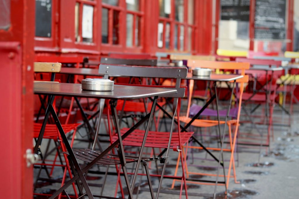A Parisian cafe terrce. The walls are painted bright red and the tables and chairs are painted in a mix of different colors. In the distance, we see the menu, written on the traditional slate, although we can't read the words.
