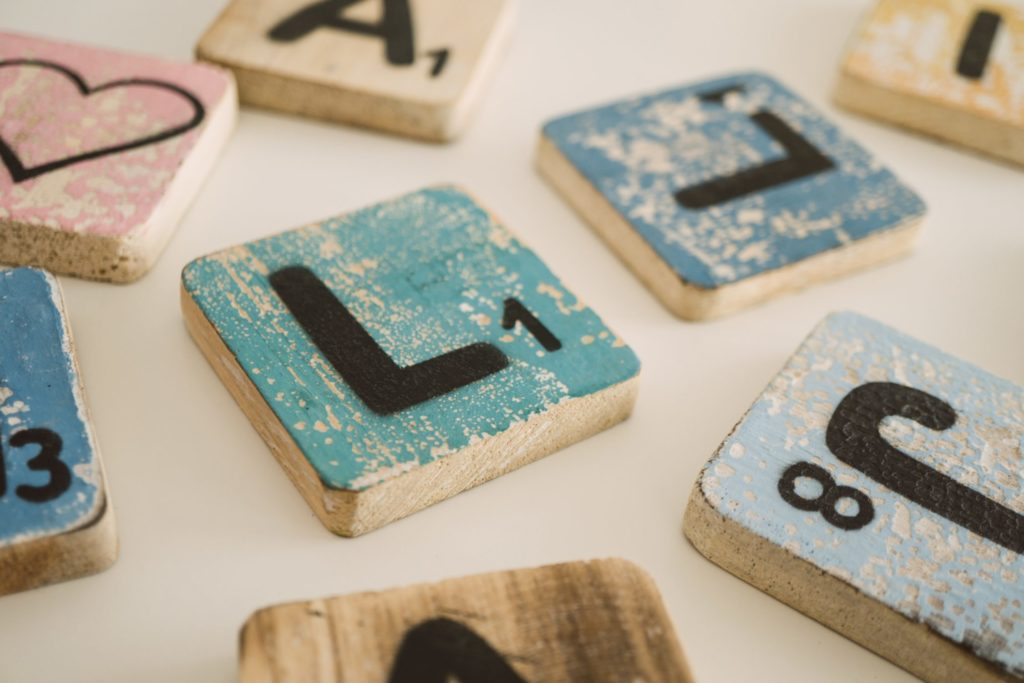 Scattered wooden letter tiles painted in different pastel colors with small numbers on each, as if for a DIY Scrabble game. One also has a drawing of a heart.