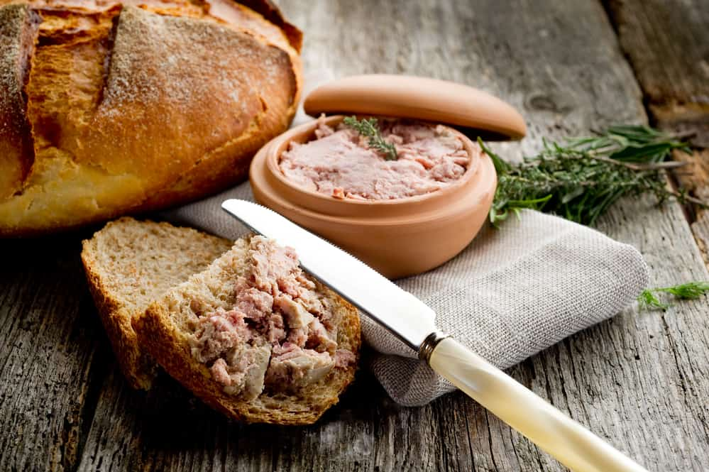 Pate de campagne in a decorative clay pot and spread on a slice of freshly baked bread.