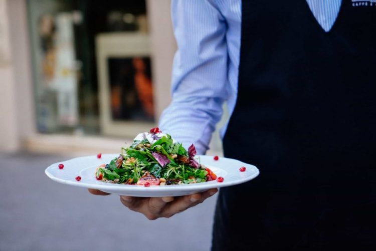 A close-up on a waiter's torso and arm. In his outstretched hand he's holding a plate wtih a salad garnished with tiny red berries - very pretty plating.