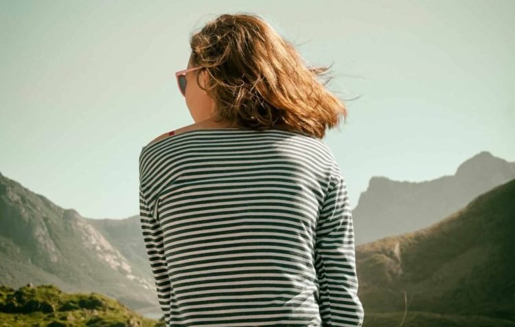 A woman with wind-blown shoulder-length blonde hair, wearing a blue and white striped shirt and sunglasses looks contemplatively at the mountainous landscape in front of her.