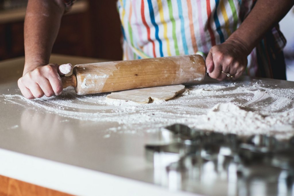 A person with a rainbow-striped apron uses a rolling pin to flatten dough. We only see their forearms, hands, and the flour-covered contertop, as well as some blurry cookie cutters in the foreground.
