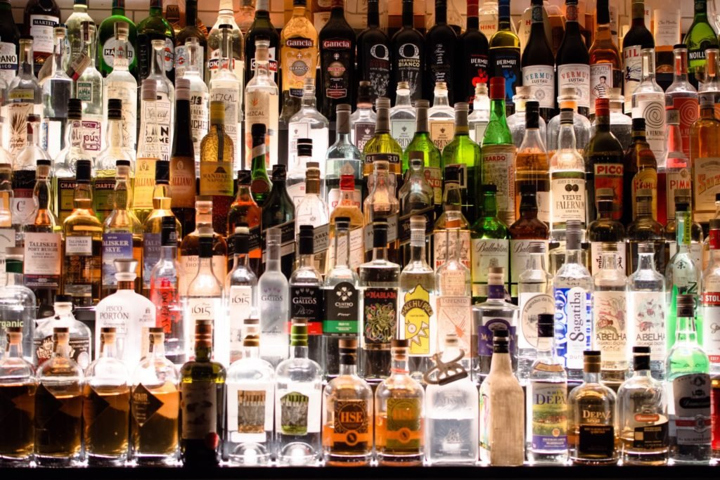 A backlit wall of bottles of alcohol.