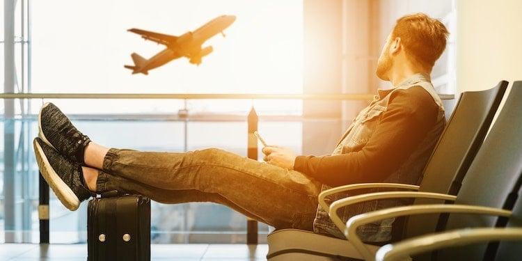 Man in airport looking at plane departing