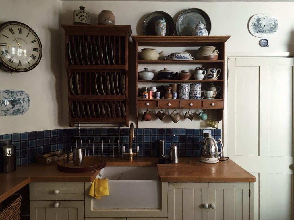 A kitchen countertop and sink. Above it we see a shelf with dishes, bowls, and other vessels. On the left side is a mounted wall clock. The kitchen looks a bit old-fashioned and like something in a French farmhouse.