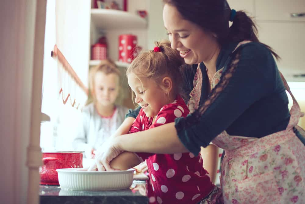 An adult woman, probably the mom, stands behind a little girl and puts her hands over the girl's, as they mix or knead something in a ceramic baking dish. In the background, we see a kitchen shelf and another little girl looking on.