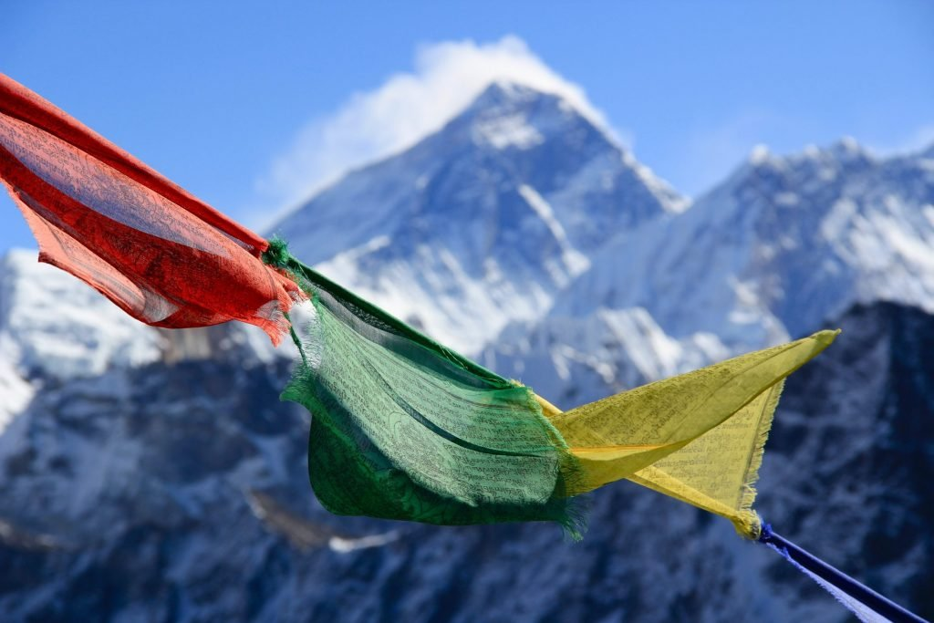 A view of the peak of Mount Everest in the distance. Three Tibetan prayer flags are in the foreground. The peak of Mount Everest is framed by a bit of cloud.